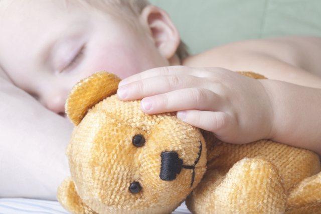 FILE: A child holds a teddy bear.