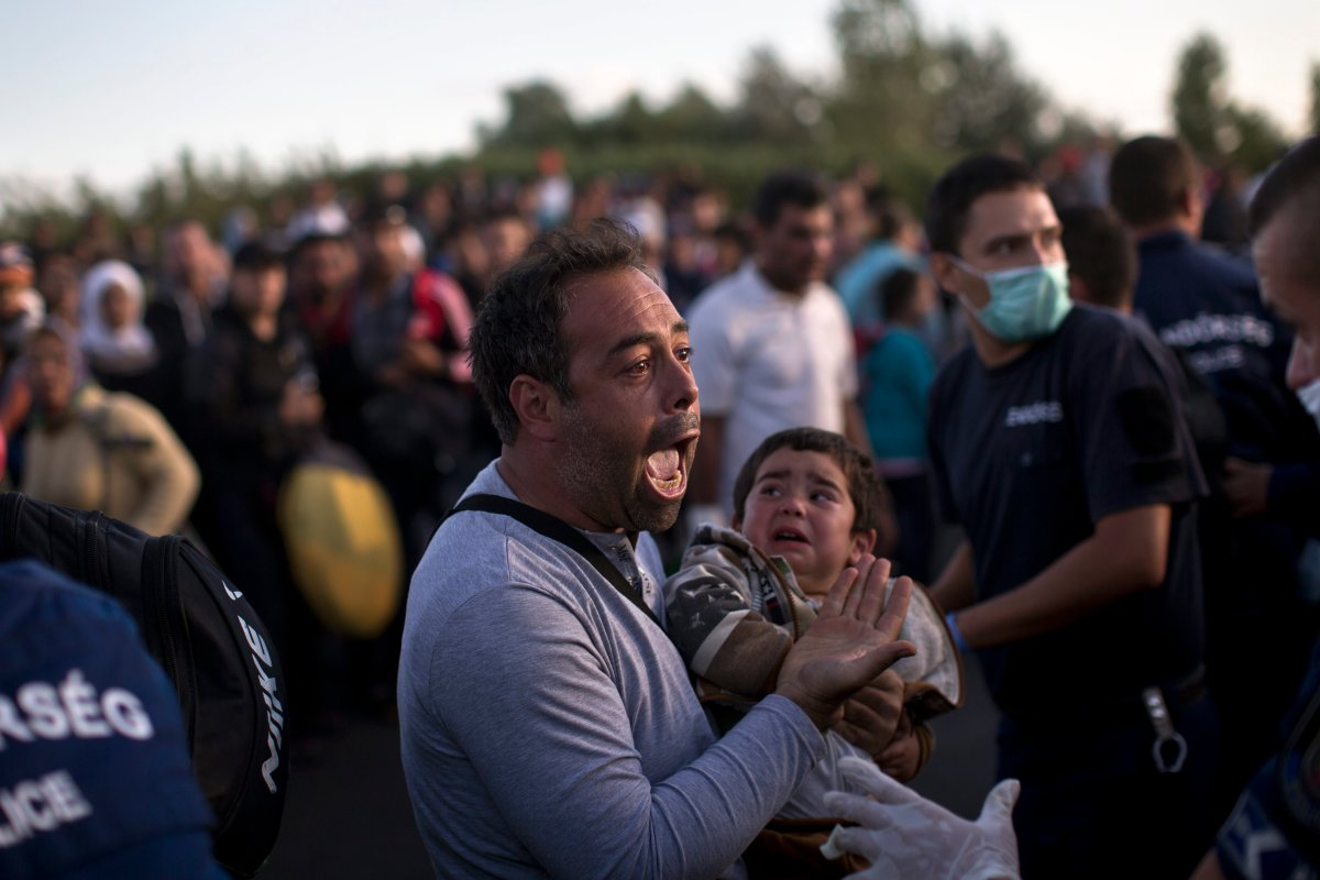 A man holds his child as he tries to talk to Hungarian police officers in Roszke, Hungary, Monday, Sept. 7, 2015, as the migrants move away from a temporary holding center controlled by Hungarian authorities, just over the border from Serbia.  The situation is confused with many hundreds of migrants moving in several directions and trying to reach a migrant registration camp, rather than wait for a unreliable bus service.