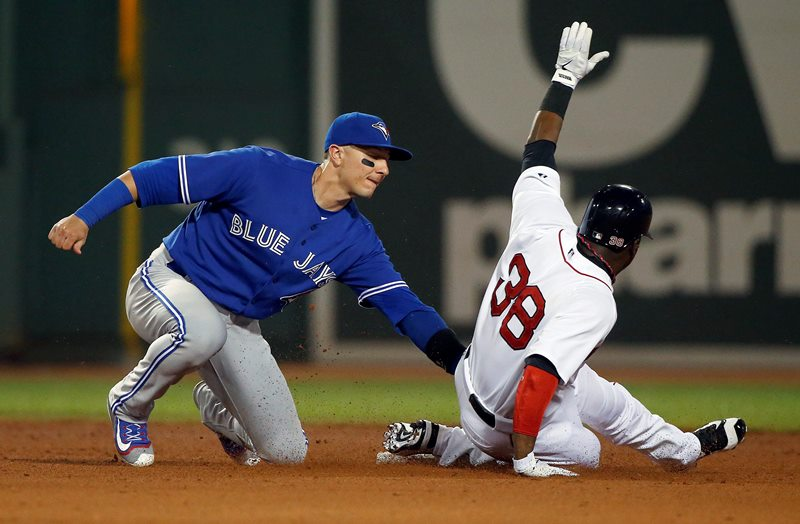 Toronto Blue Jays' Troy Tulowitzki, left, catches Boston Red Sox's Rusney Castillo (38) trying to steal second base during the ninth inning of a baseball game in Boston, Tuesday, Sept. 8, 2015.