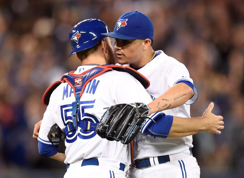 Toronto Blue Jays' closing pitcher Roberto Osuna embraces catcher Russell Martin after winning the game against the New York Yankees in Toronto on Monday, Sept. 21, 2015.