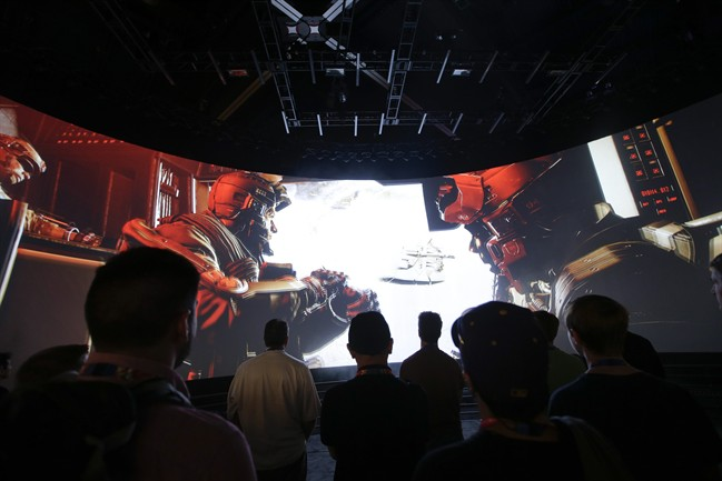 """People watch the """"Call of Duty: Advanced Warfare"""" video game trailer at the Activision booth at the Electronic Entertainment Expo, in Los Angeles."""