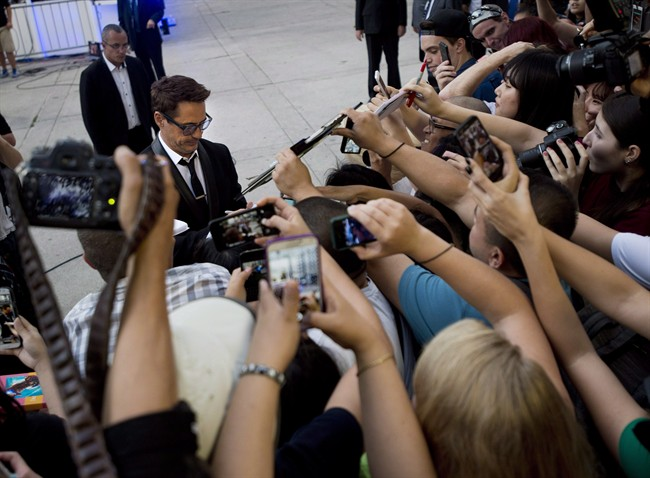 """Actor Robert Downey Jr., centre, signs autographs for fans after arriving on the red carpet for his new movie """"The Judge"""" during the 2014 Toronto International Film Festival in Toronto on Thursday, September 4, 2014. Starting Thursday, Toronto will host its 40th TIFF."""