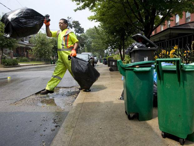 File photo of a garbage collector picking up bags in the city.