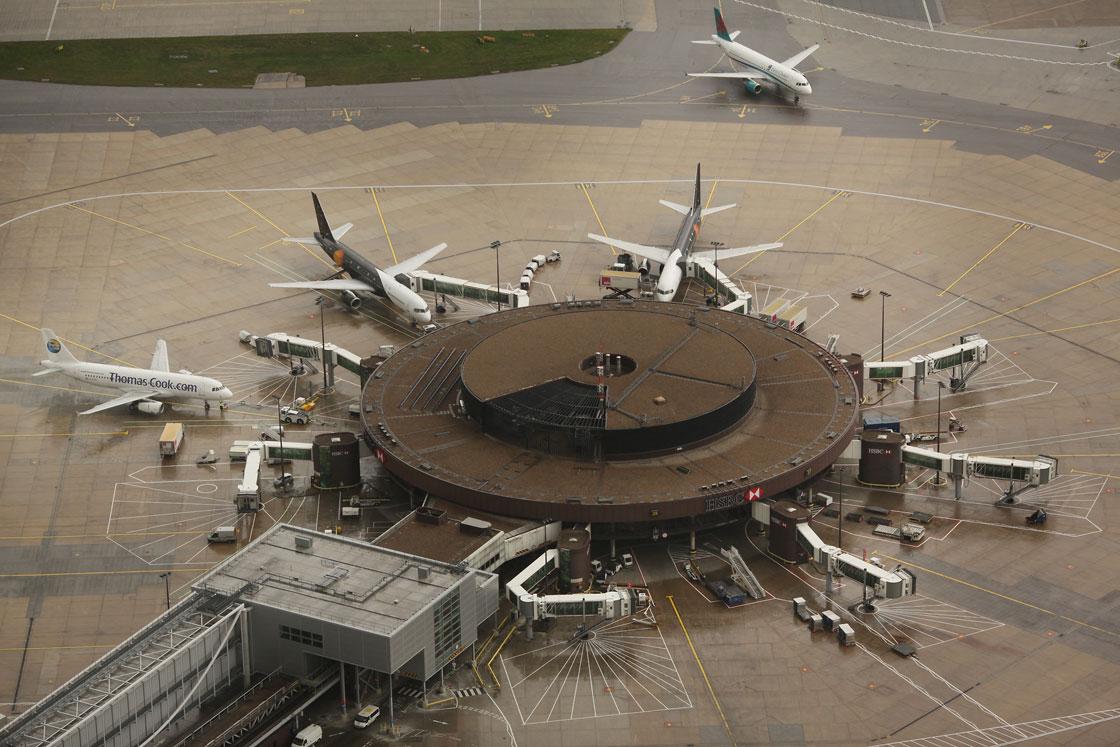 Passenger aircraft surround satellite gates at Gatwick Airport.
