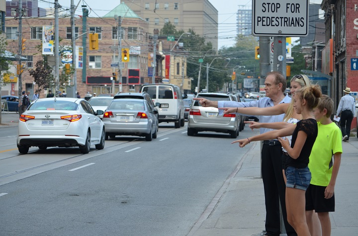 Norm Kelly demonstrate the finger pointing technique for pedestrians  at crosswalks.