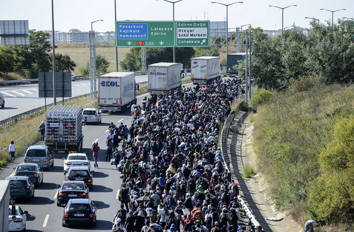 Syrian migrants and refugees march along the highway towards the Turkish-Greek border at Edirne on September 18, 2015.