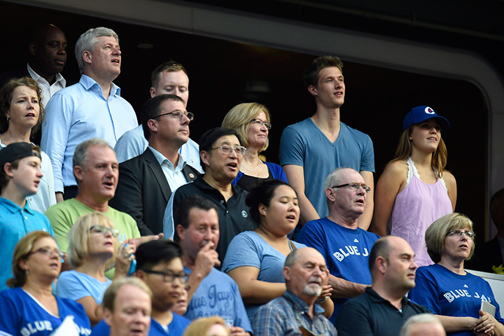 Conservative Leader Stephen Harper and his family sing the national anthem as the Toronto Blue Jays prepare to take on the Cleveland Indians during American League baseball action in Toronto on Monday, August 31, 2015.