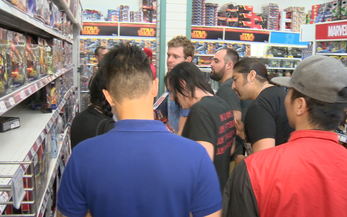 """A crowd of shoppers surround a Star Wars toy display at a Toys """"R"""" Us store in Toronto, Canada on Sept. 4, 2015."""