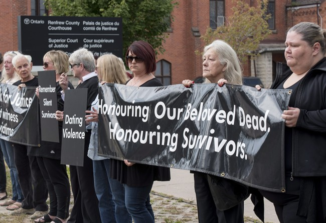 Mourners opposing violence against women stand in solidarity at the courthouse in Pembroke, Ont. on Wednesday, Sept. 23, 2015, as Basil Borutski, 57, who led police on a five hour manhunt Tuesday and is accused of killing three women, is set to appear in court.