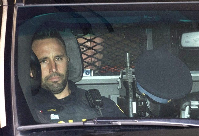 Basil Borutski looks out from behind the mesh enclosure in the back of a police vehicle after appearing at the courthouse in Pembroke, Ont. on Wednesday, Sept. 23, 2015.