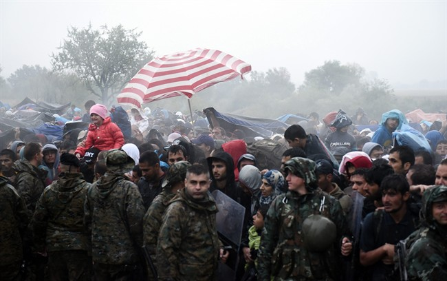 Refugees and migrants wait to pass from the northern Greek village of Idomeni to southern Macedonia, Thursday, Sept. 10, 2015.