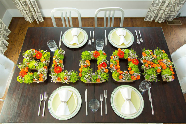 """This photo provided by HGTV.com shows a tabletop with a """"bloom"""" centerpiece made from shortly cut flowers inserted into floral foam inside of papier-mache letters whose fronts have been removed. A single letter can be used as a monogram centerpiece or letters can spell out party themes."""