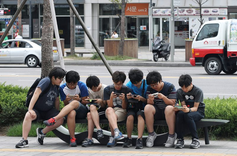 In this July 16, 2015, file photo, South Korean high school students play games on their smartphones on a bench on the sidewalk in Seoul, South Korea.