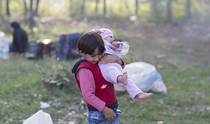 A Syrian refugee girl carries her sister as refugees rest at Sarayici Park, as they wait for permission to pass the Turkish-Greek border in Edirne, Turkey, 20 September 2015.