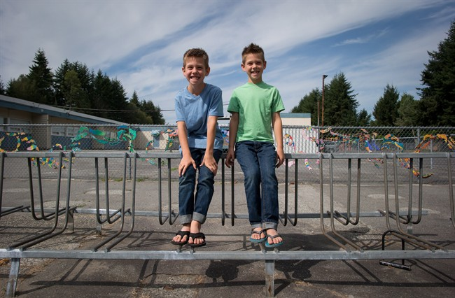 Twin eight-year-old brothers Riley, left, and Taylor Dalby sit for a photograph outside South Park School where they will enter Grade 3 this year, in Delta, B.C., on Monday August 24, 2015.