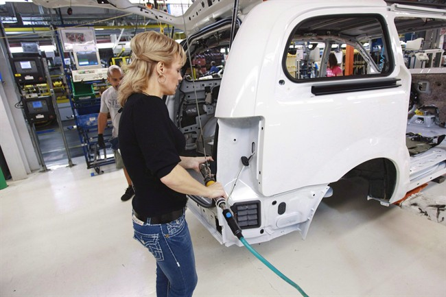 A worker on the production line at Chrysler's assembly plant in Windsor, Ontario, works on a minivan on Tuesday, January 18, 2011.