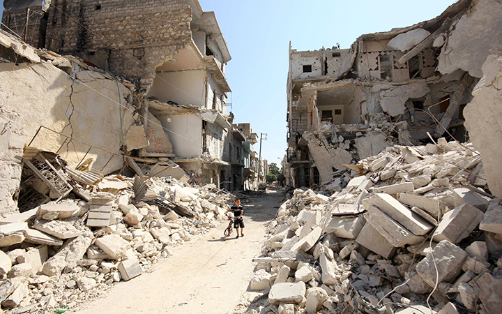 A Syrian boy plays between the rubble of destroyed houses following a reported barrel-bomb attack by Syrian government forces, in the Tariq al-Bab neighbourhood in the northern city of Aleppo on Aug. 21 2015.