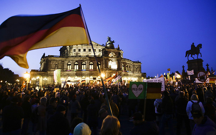 A protestor waves a German flag as he attends a demonstration of PEGIDA (Patriotic Europeans against the Islamization of the West) in front of the Semperoper, Dresden's famous opera house, in Dresden, Germany, Monday, Oct. 12, 2015.
