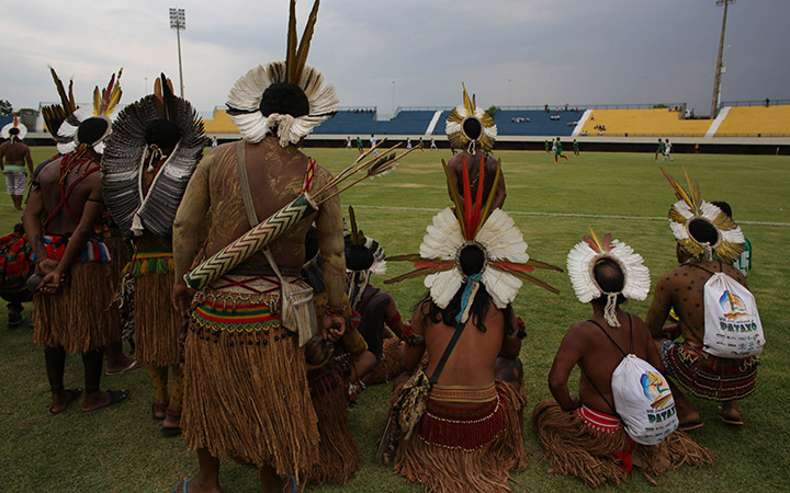"""Pataxo men watch a soccer match against a fellow Brazilian tribe, Xerente, during the World Indigenous Games, in Palmas, Brazil, Friday, Oct. 23, 2015. Hundreds of indigenous people from across Brazil and delegations from as far afield as Mongolia and the Philippines have already arrived for what has been billed as the first """"indigenous Olympics.""""."""