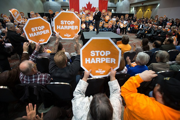 """Supporters wave a """"Stop Harper"""" signs as NDP leader Thomas Mulcair speaks at a rally in London, Ontario October 4, 2015."""
