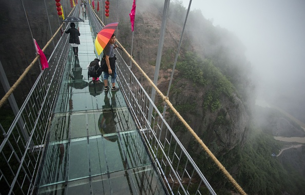 Chinese tourists walk across a glass-bottomed suspension bridge in the Shinuizhai mountains in Pingjang county, Hunan province some 150 kilometers from Changsha on October 7, 2015. The bridge, originally a wooden walkway spanning some 300 meters across the 180-meter deep valley, reopened two weeks ago following renovations as a glass-bottomed tourist attraction.