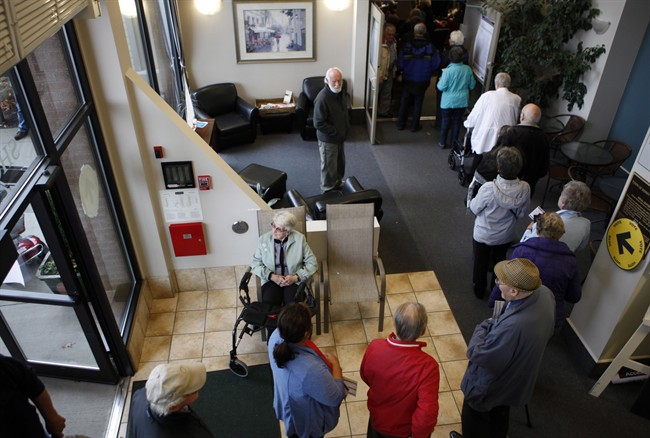 Voters form a line as they wait to cast their ballots in Sidney, B.C., Monday, Oct. 19, 2015.