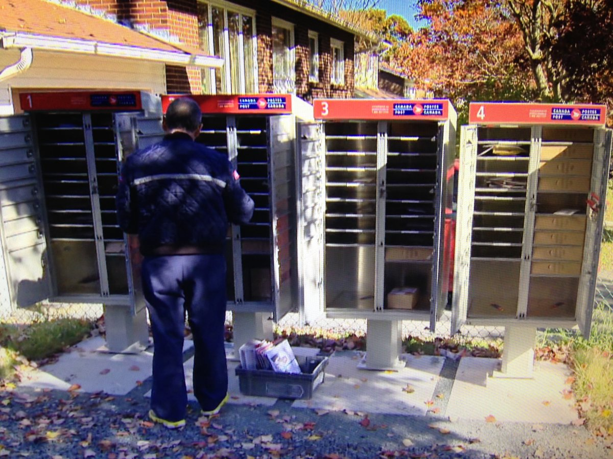 A letter carrier puts mail in a community mailbox.