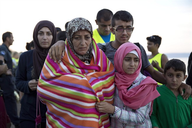 A Syrian family walks after they arrived with other refugees from Turkey to the shores of the Greek island of Lesbos, on a inflatable dinghy, Friday, Sept. 25, 2015.