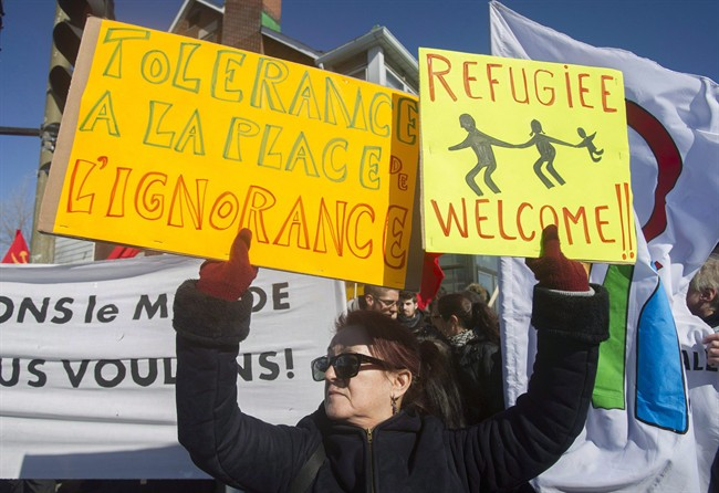 A woman holds up signs during a demonstration to denounce the anti-Islam group PEGIDA in Montreal on March 28, 2015.