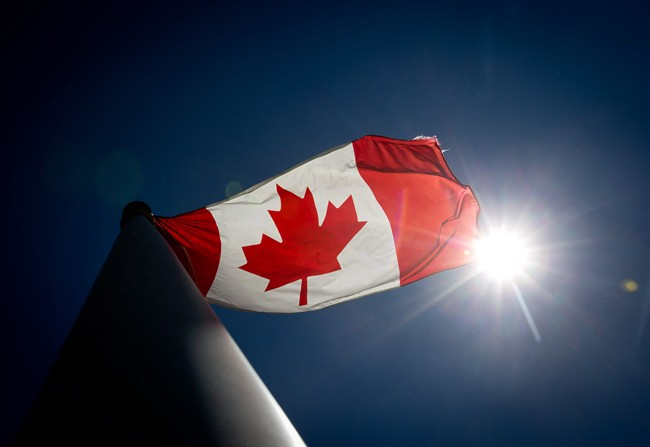 A Canadian flag flies in the wind at Granville Island in Vancouver, B.C., on Monday June 30, 2014. A Canadian flag was removed from a Manitoba advance polling station over the weekend because a worker felt it violated election rules.