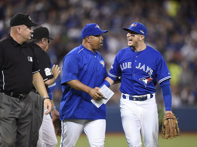 Toronto Blue Jays shortstop Troy Tulowitzki, right, is held back by bench coach DeMarlo Hale after being tossed from the game during eighth inning game three American League Championship Series baseball action against the Kansas City Royals in Toronto on Monday, Oct. 19, 2015.