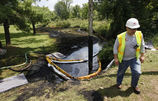 FILE - In this July 29, 2010 file photo, a worker monitors the water in Talmadge Creek in Marshall Township, Mich., near the Kalamazoo River as oil from a ruptured pipeline, owned by Enbridge Inc, is vacuumed out the water. The U.S. Department of Transportation wants to expand rules for pipelines carrying oil, gasoline and other hazardous liquids inspections requirements to include rural areas that are currently exempt, and for companies to more closely analyze the results of their inspections.