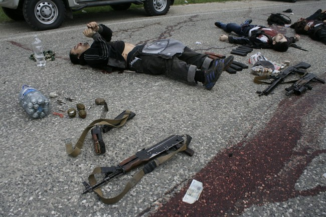 In this Thursday, May 9, 2013, file photo bodies of killed militants lie surrounded by different kinds of explosives and weapons at Gubden in Dagestan, Russia.