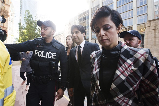 Police escort former CBC radio host Jian Ghomeshi, centre, who appears with his lawyer Marie Henein, right, for his pre-trial hearing for his sexual assault case in Toronto on Thursday, October 1, 2015.