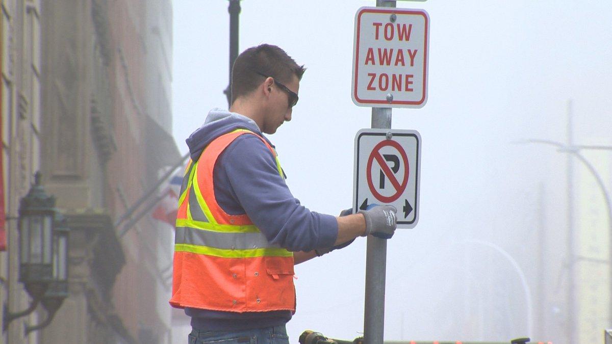 "A city worker installs a ""No Parking"" sign on the Hollis Street bike lane."