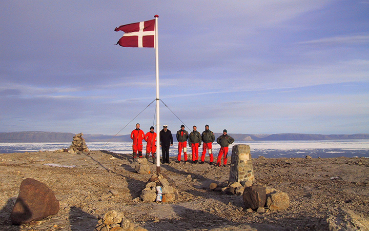 The crew of Danish warship Vedderen perform a flag raising ceremony on the uninhabitated Hans Island off northwestern Greenland, in this Aug. 13, 2002 file photo.