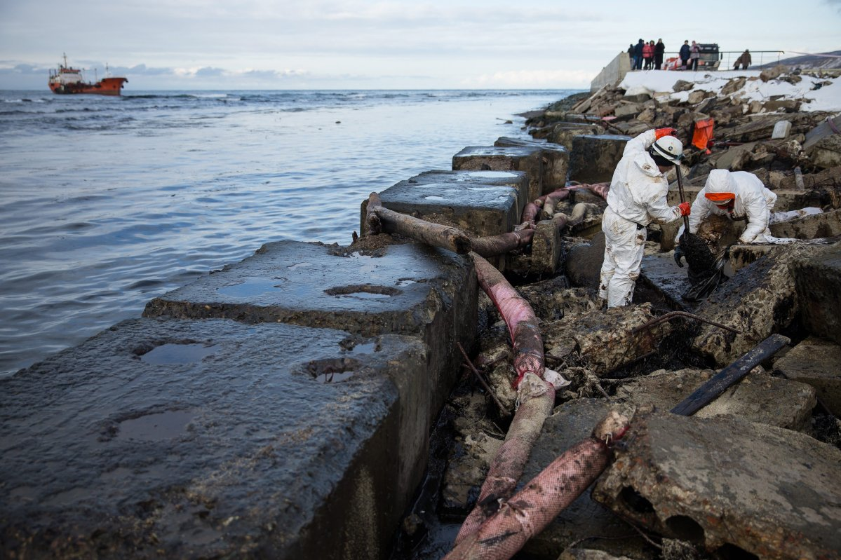 Workers remove crude oil along the shoreline during a clean up operation after the tanker Nadezhda, left, hit a reef during a storm on Saturday near the port city of Nevelsk, about 90 kilometres (56 miles) south west of Yuzhno-Sakhalinsk, Sakhalin Island in Russia's Far East, Sunday, Nov. 29, 2015. Russian emergency services say cleanup operations are underway after an oil tanker was grounded, damaging one of its fuel tanks, carrying 786 tons of fuel oil and diesel fuel.
