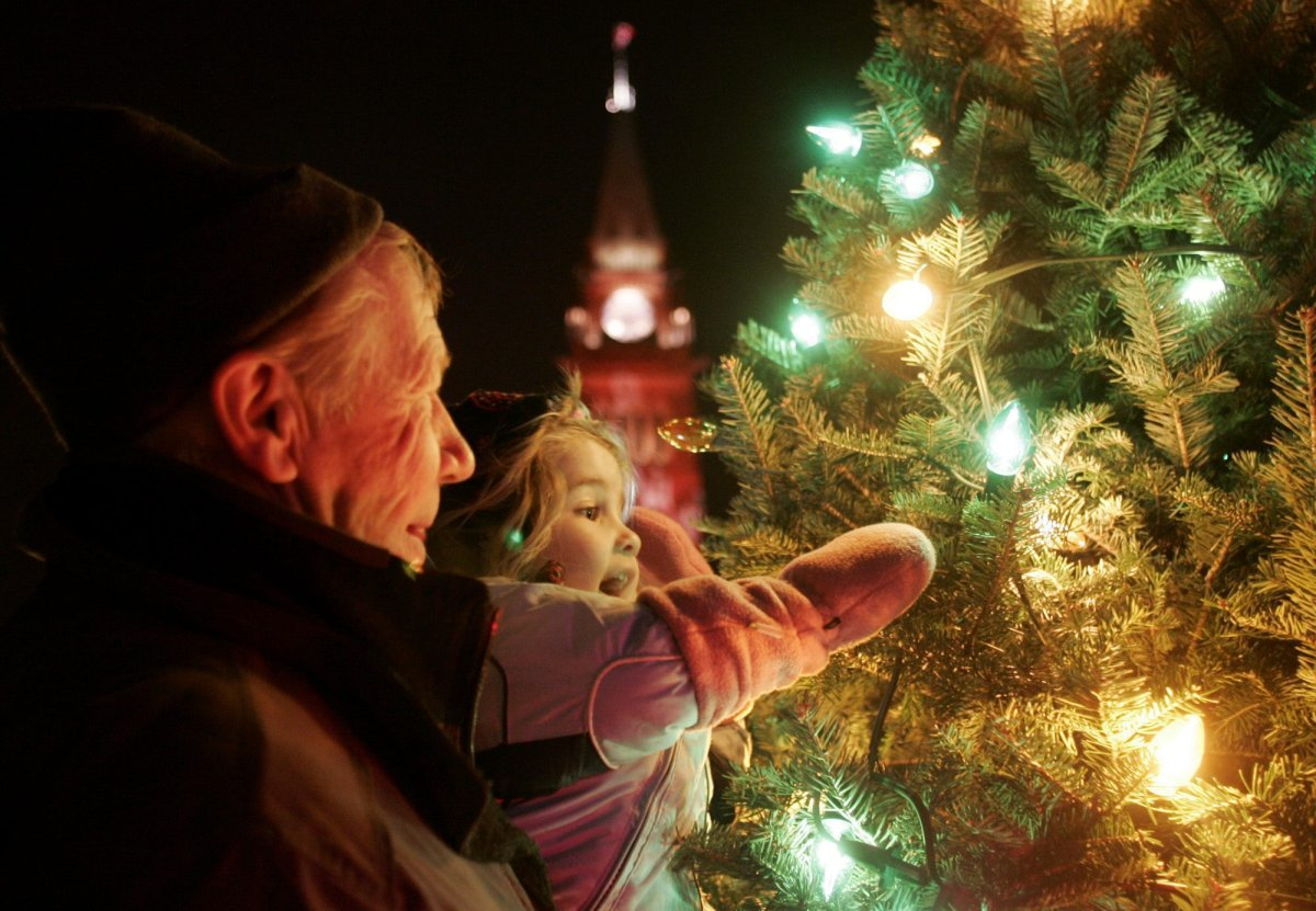 FILE: A child and her grandfather view Christmas lights on a spruce tree.