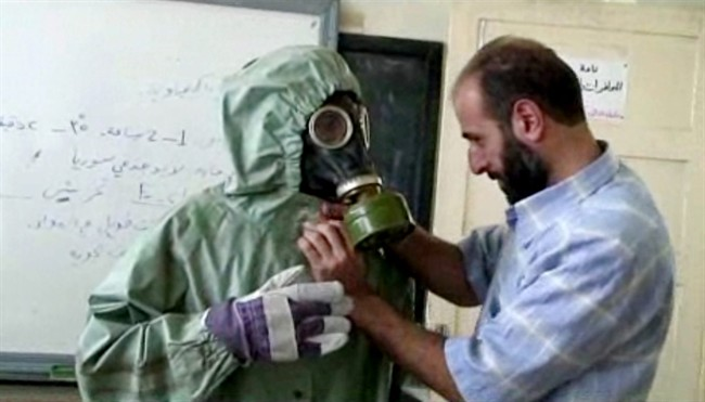 This image made from an AP video posted on Wednesday, Sept. 18, 2013 shows a volunteer adjusting a students gas mask and protective suit during a session on reacting to a chemical weapons attack, in Aleppo, Syria. Russia and China have blocked a UN resolution that would have imposed sanctions on 21 Syrian individuals, organizations and companies allegedly involved in chemical weapons attacks.
