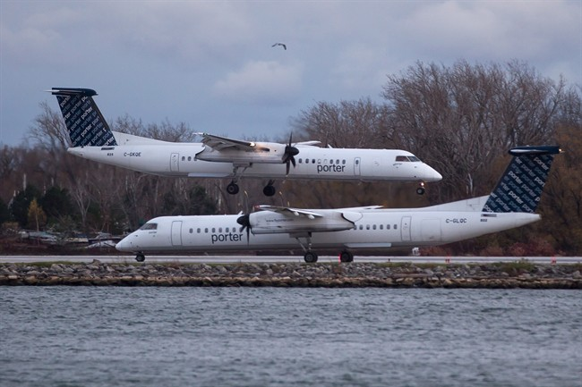 A Porter Airlines plane lands next to a taxiing plane at Toronto's Island Airport on Friday, November 13, 2015. The future of Bombardier's sole Canadian CSeries order is in serious doubt after Ottawa confirmed it would not allow passenger jets to fly out of Billy Bishop Toronto City Airport.