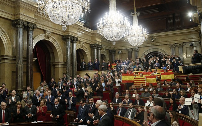 Popular Party of Catalonia, right, show Spanish flags and Catalonia flags at the end of a parliamentary session at the Parliament in Barcelona, Spain, Monday, Nov. 9, 2015.