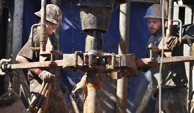 Feb. 21, 2012 file photo of oil field workers  using a drill.