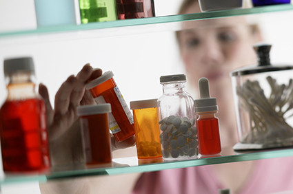 Woman taking pills from medicine cabinet.