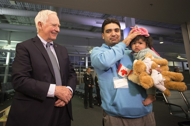Governor General David Johnston meets Syrian refugee Osama and his baby daughter as they arrive at the Welcome Centre at Toronto's Pearson Airport on Friday December 18, 2015. A new report examines the experiences of Canada's Syrian refugees.