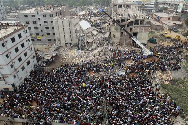 In this April 25, 2013 file photo, Bangladeshi people gather as rescuers look for survivors and victims at the site of a building that collapsed a day earlier, in Savar, near Dhaka, Bangladesh.
