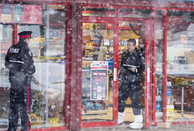 Homicide detectives investigate at a Mac's convenience store in Edmonton on Friday, December 18, 2015. A 13-year-old cried as he appeared briefly in youth court accused of killing two convenience store clerks.The boy, who cannot be identified, faces charges that include first-degree murder and robbery.THE CANADIAN PRESS/John Ulan.