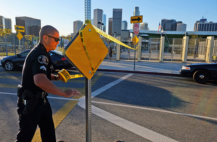A police officer puts up yellow tape outside of Edward Roybal High School in Los Angeles, on Tuesday morning, Dec. 15, 2015.