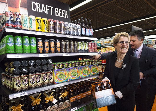 Ontario Premier Kathleen Wynne, left, and Minister of Finance Charles Sousa, right, pick beer at a Loblaws grocery store in Toronto on Tuesday, December 15, 2015.