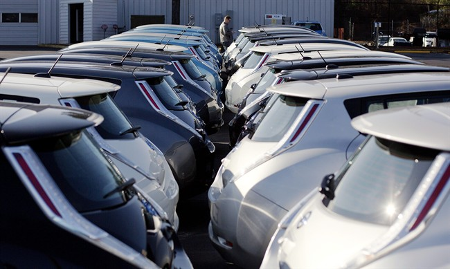 FILE - In this file photo, electric vehicles sit on display at an auto dealership.