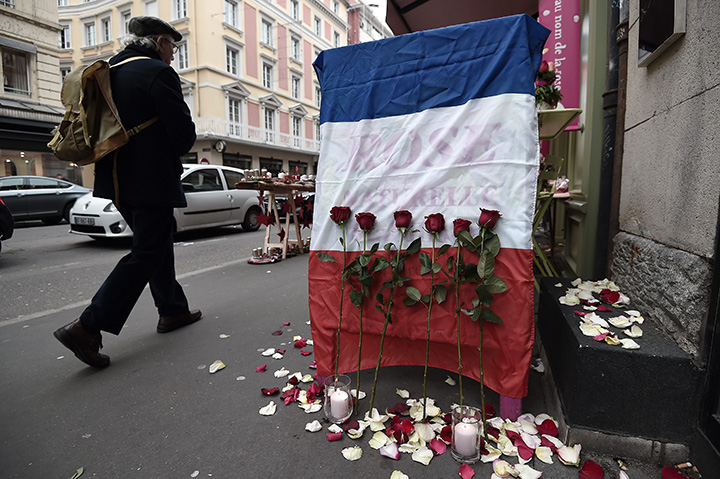 A man walks past a French national flag put outside a flower shop on November 27, 2015 in Strasbourg, eastern France, during the National Tribute to the 130 people killed in the November 13 Paris attacks.